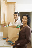 Indian couple unpacking grocery bags in kitchen — Stok fotoğraf