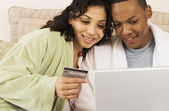 African couple with credit card using laptop in bed — Stock Photo