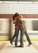 Couple hugging at train station — Stockfoto