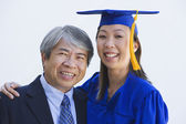 Asian woman in graduation cap and gown with father — Stock Photo