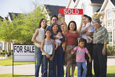 Multi-generational Asian family holding up Sold sign in front of house — Stok fotoğraf