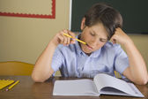 Hispanic boy doing schoolwork in classroom — Foto Stock