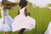 Young girls wearing party dresses and playing in field — Stock Photo