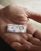 Man's hand holding tiny British Pound — Stock Photo