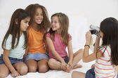 Group of young girls using video camera — Stock Photo
