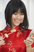 Asian teenaged girl dialing cell phone — Stock Photo