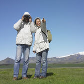 Couple using binoculars and wearing winter jackets with snow-capped mountains in background — ストック写真