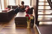 Kobieta siedzi na kanapie — Zdjęcie stockowe