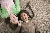 Two girls lying on the floor laughing — Stock Photo