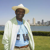 Senior African man with camera and binoculars around neck and cityscape in background — Stock Photo