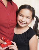 Young Asian girl giving mother gift — Stock Photo