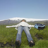 Woman wearing winter jacket laying in grass next to backpack — Stock Photo