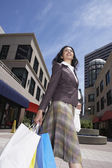 Indian woman in urban scene with shopping bags — Stock Photo