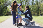 Hispanic father helping daughter fasten bicycle helmet — Stock Photo