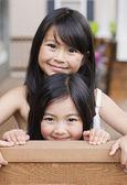 Jóvenes hermanas asiáticas abrazando y sonriente en el interior — Foto de Stock