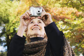 Senior woman taking photograph outdoors — Stock Photo