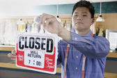 Asian drycleaner putting up closed sign — Stock Photo
