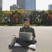 Asian man sitting on ground using laptop in urban area — Stock Photo