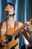 Asian woman playing guitar and singing — Stock Photo