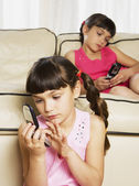 Young Hispanic sisters using cell phones on sofa — Stock Photo
