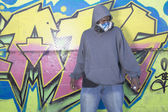 African man with spray paint next to graffitied wall — Stock Photo