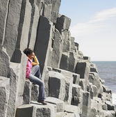 Woman sitting on rock ledge next to water — Stock Photo