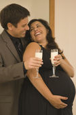 Pregnant couple in fancy clothing toasting champagne glasses of milk — Stock Photo