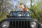 Grandparents and grandson standing in jeep — Stock Photo