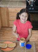 Hispanic girl making peanut butter and jelly sandwich — Stock Photo