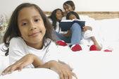 Chica afroamericana en cama con familia detrás de ella — Foto de Stock