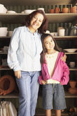 Hispanic mother and daughter in pottery shed — Stock Photo