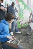 Young man with music equipment and friends next to graffitied wall — Stock Photo