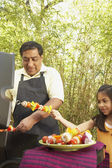Hispanic father and daughter grilling kebabs — Stock Photo