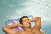 Indian man on float in swimming pool — Stock Photo