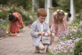 Children gathering Easter eggs in garden — Stock Photo