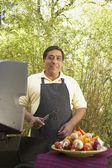 Hispanic man next to barbecue grill with kebabs — Stock Photo