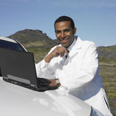 Man in lab coat using laptop on car hood in deserted rural area — Stok fotoğraf