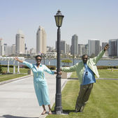 Senior African couple holding onto lamp post with cityscape in background — Stock Photo