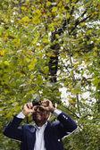 Senior African man using binoculars in woods — Stock Photo