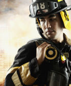 Male fire fighter in front of burning building — Stock Photo