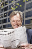 Middle-aged businessman reading newspaper outdoors — Stock Photo