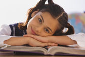 Young Hispanic girl at desk in classroom — Stok fotoğraf