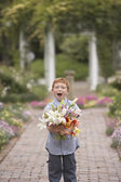 Young boy holding flowers in garden — Stock Photo
