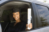 African woman in car wearing graduation outfit — Stock Photo