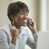 African businesswoman using telephone and cheering — Stock Photo