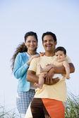испаноязычное родителей, держа ребенка на открытом воздухе — Стоковое фото