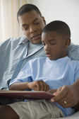 African father reading to son — Stock Photo