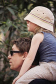 Father carrying young daughter on shoulders — Stock Photo
