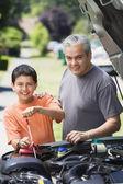 Hispano padre e hijo revisar aceite en coche — Foto de Stock