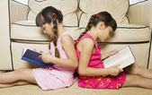 Two young sisters reading back to back — Stock Photo